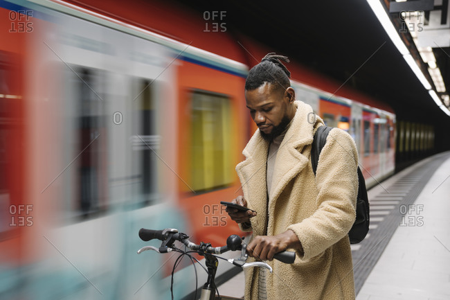 Stylish man with a bicycle and smartphone in a metro station