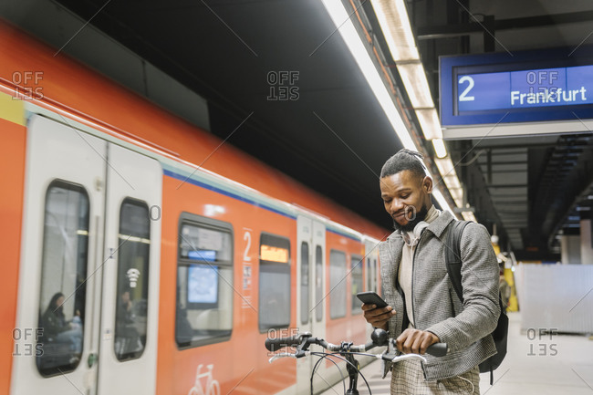 Stylish man with a bicycle- headphones and smartphone in a metro station