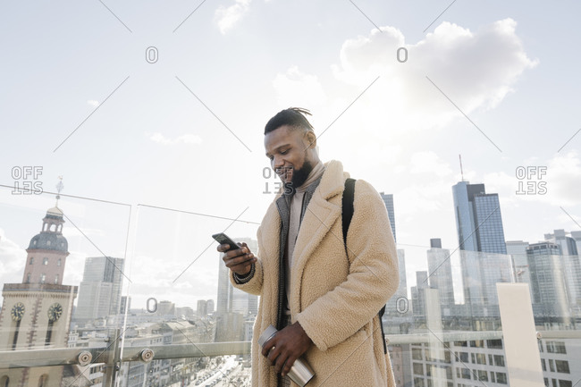 Stylish man using smartphone on observation terrace with skyscraper view- Frankfurt- Germany