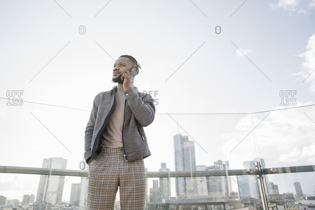 Stylish man on the phone on observation terrace with skyscraper view- Frankfurt- Germany