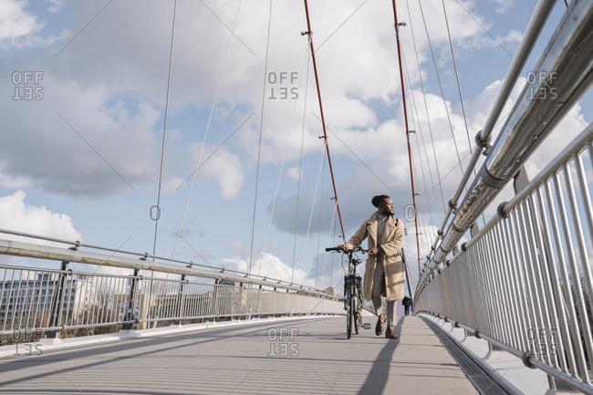 Stylish man with a bicycle walking on the bridge