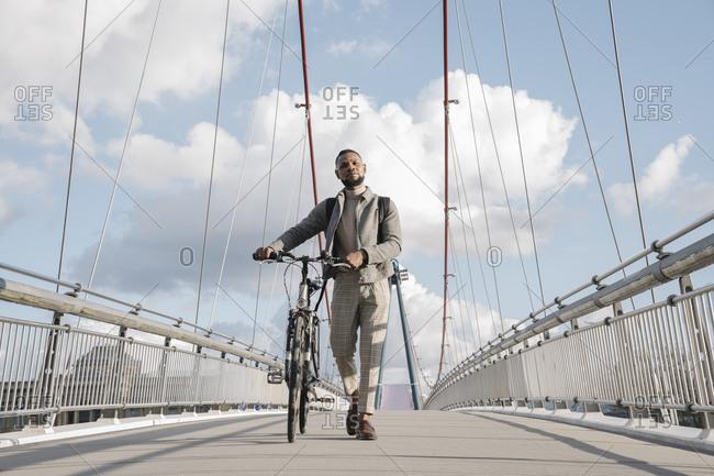 Stylish man with a bicycle walking on a bridge