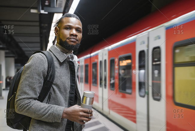 Stylish man with reusable cup and headphones in a metro station