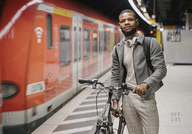 Stylish man with a bicycle and headphones in a metro station