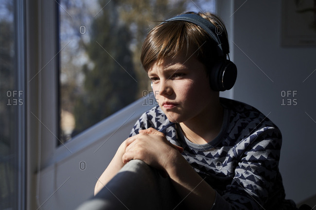 Portrait of pensive boy listening music with headphones while looking out of window