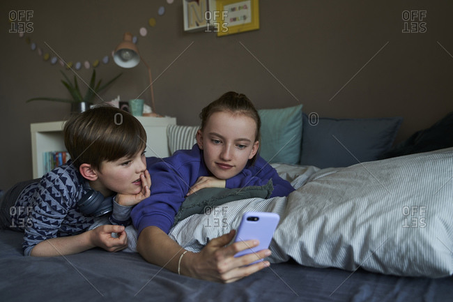 Portrait of brother and his older sister lying together on bed using smartphone for video chat