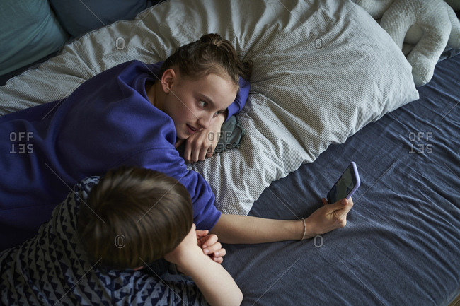 Siblings lying together on bed using smartphone for video chat