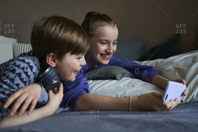 Laughing siblings lying together on bed using smartphone for video chat