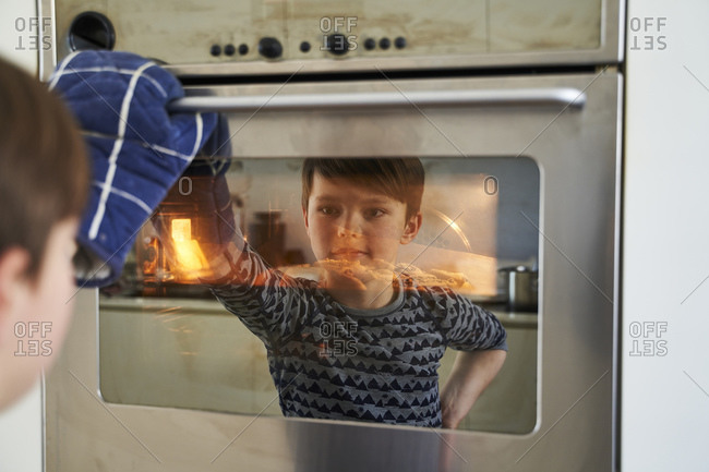 Mirror image of proud boy watching cake in oven