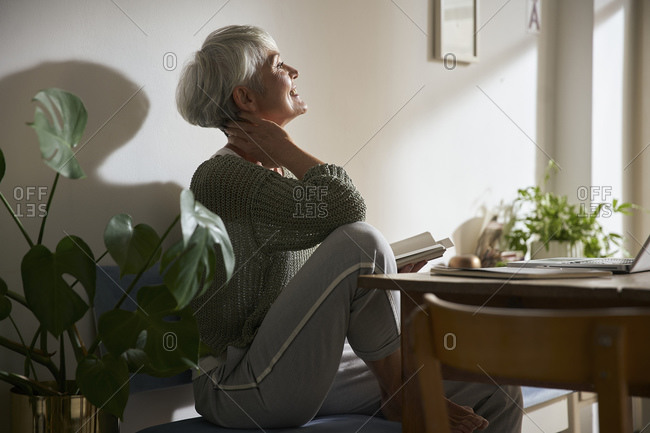 Confident senior woman with notebook and laptop relaxing at home