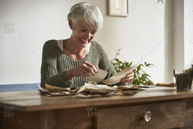 Portrait of happy senior woman sitting at table at home watching old photos