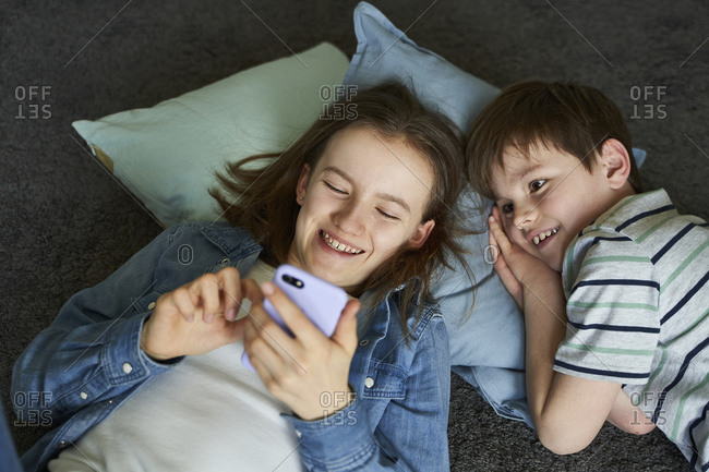 Portrait of laughing girl and her little brother lying together on the floor  looking at smartphone