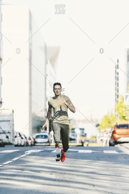Disabled athlete with leg prosthesis exercising in the city running on a street
