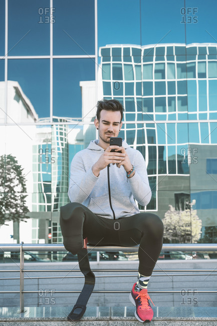 Disabled athlete with leg prosthesis having a break from exercising in the city using cell phone