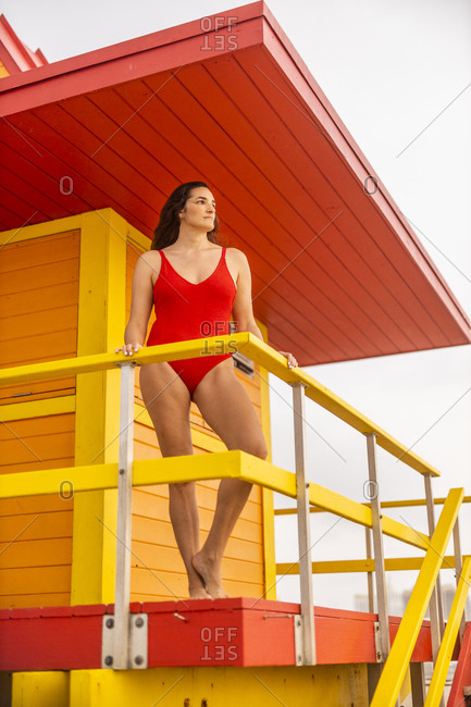 Portrait of woman in red swimsuit on lifeguard hut on Miami Beach- Miami- Florida- USA