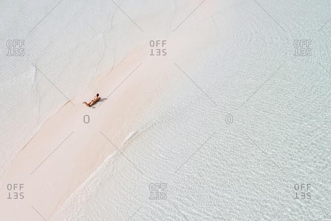 Woman sunbathing on white sand bank in the sea- Bahamas- Caribbean