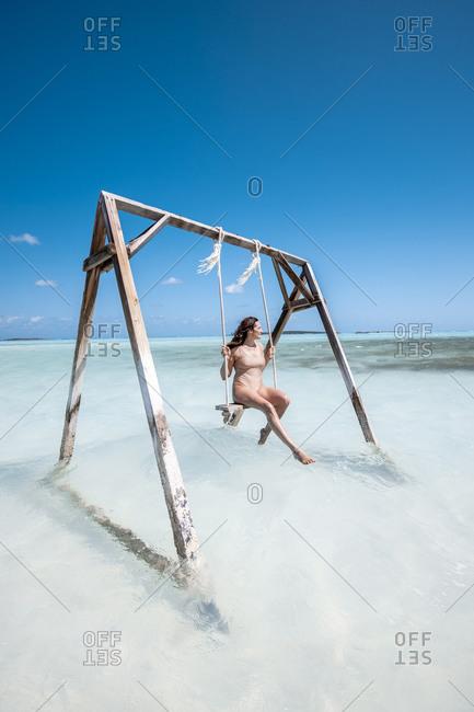 Woman swinging on swing in the sea- Bahamas- Caribbean