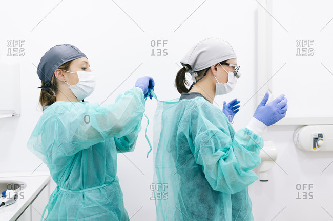 Two dentists putting on sterile protective clothing