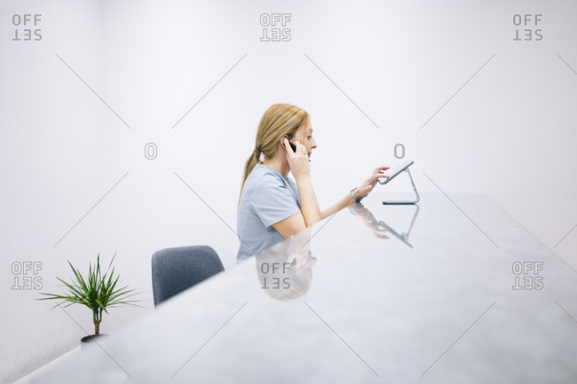 Receptionist at reception desk of a medical practice using headset and digital device