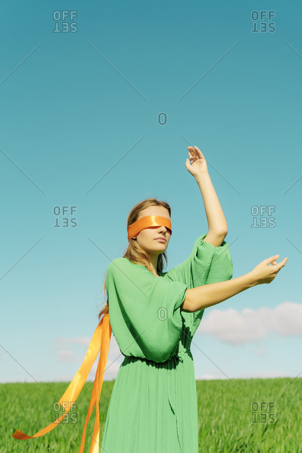 Blindfolded young woman wearing a green dress standing in a field