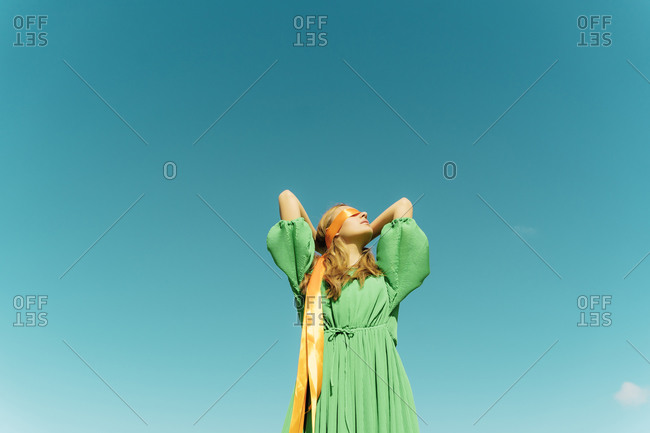 Blindfolded young woman wearing a green dress under blue sky