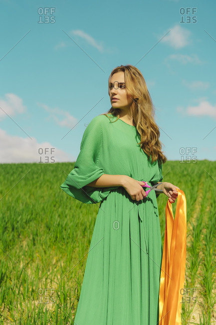 Young woman wearing a green dress standing in a field with scissors and ribbon
