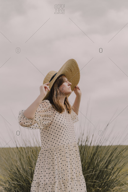 Woman with vintage dress and straw hat alone at a remote field in the countryside