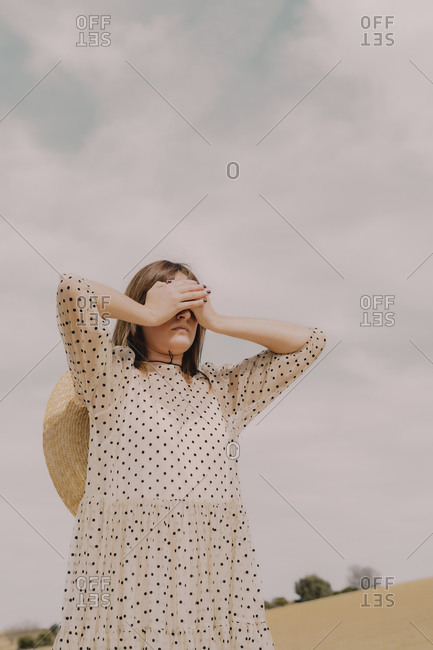 Woman in vintage dress alone at a remote field in the countryside covering her eyes