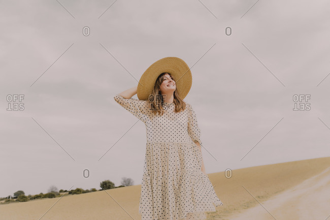 Smiling woman in vintage dress alone at a remote field in the countryside