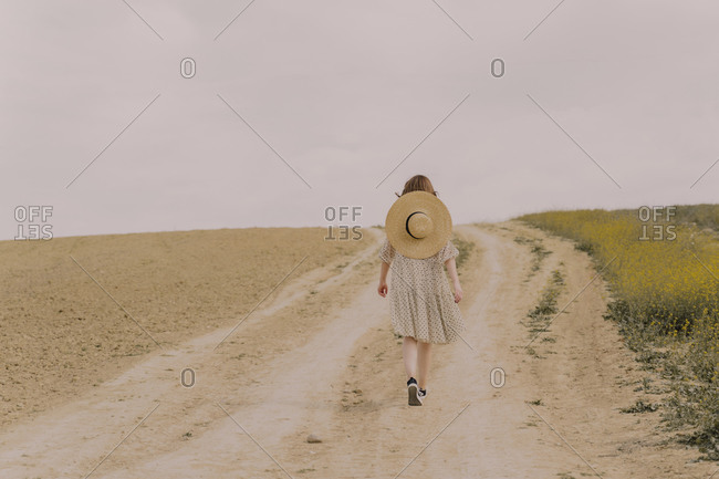 Woman with straw hat and vintage dress walking on a remote field road in the countryside