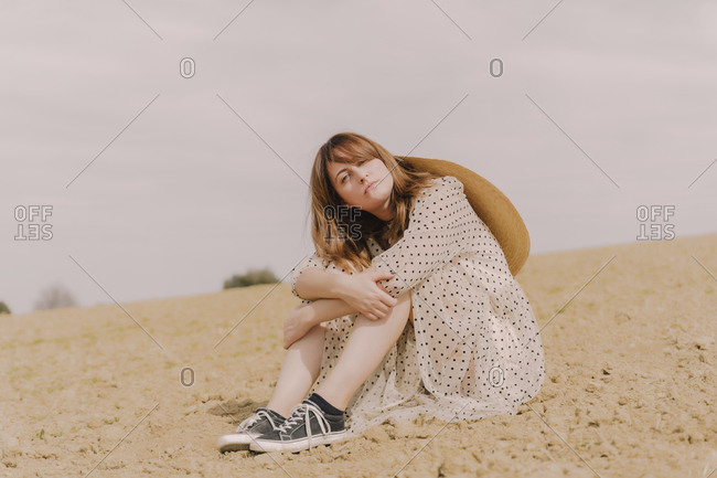 Portrait of woman in vintage dress sitting on a remote field in the countryside