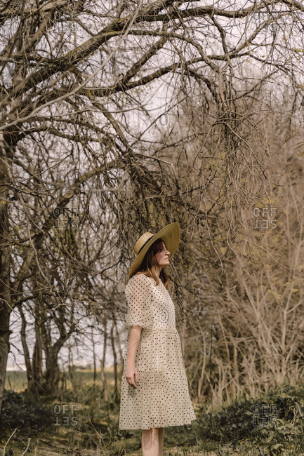 Woman with straw hat and vintage dress in the countryside