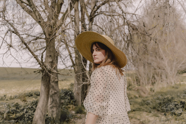 Portrait of serious woman with straw hat and vintage dress in the countryside