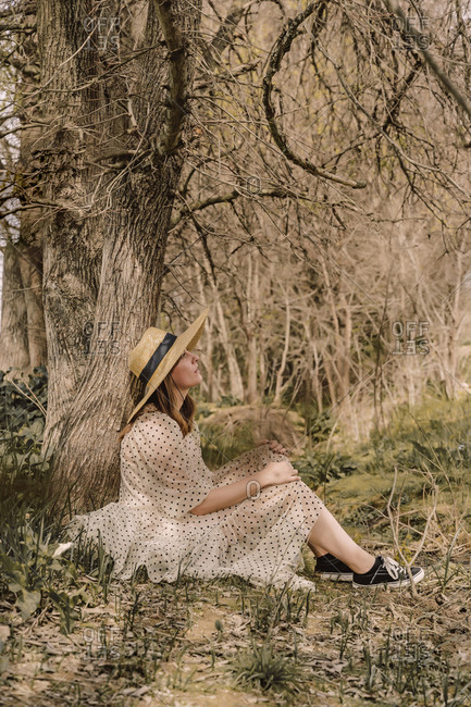 Woman with straw hat and vintage dress sitting at a tree in the countryside