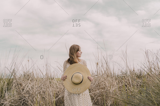 Woman in vintage dress holding straw hat at a remote field in the countryside