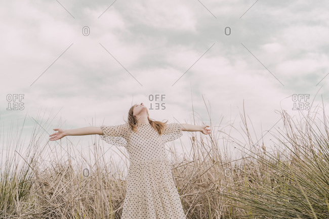 Woman in vintage dress with outstretched arms at a remote field in the countryside