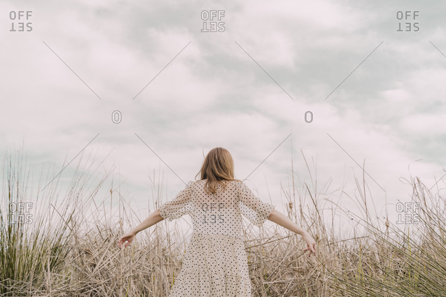 Rear view of woman in vintage dress with outstretched arms at a remote field in the countryside