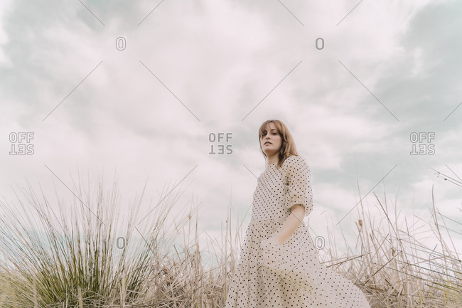 Portrait of woman in vintage dress alone at a remote field in the countryside