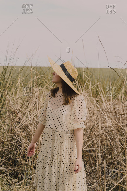 Woman with straw hat and vintage dress alone at a remote field in the countryside