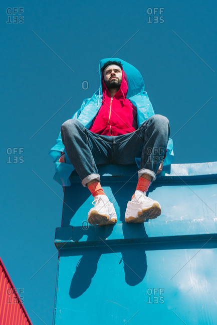 Young man wearing red hooded jacket sitting on container against blue sky