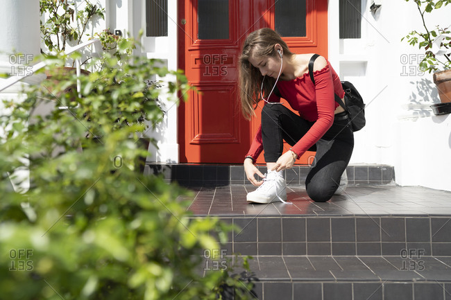 Young woman tying her shoes at house entrance