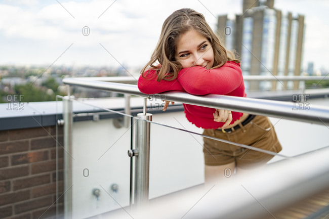 Portrait of smiling young woman leaning on railing on rooftop- London- UK