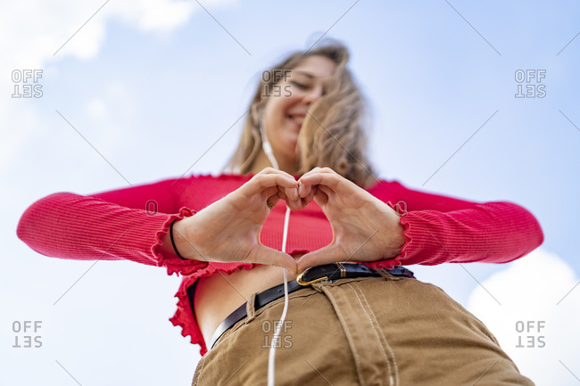 Worm's eye view of young woman listening to music with earphones shaping a heart with her hands