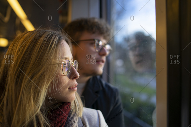Pensive young woman sitting in tram with her boyfriend looking out of window