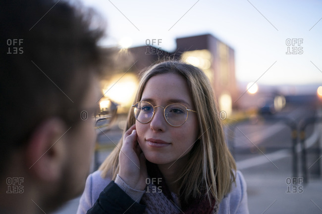 Portrait of blond young woman face to face with her boyfriend at evening twilight