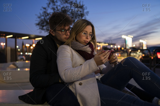 Young couple using smartphone at evening twilight