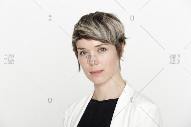 Portrait of woman with dyed short hair against white background