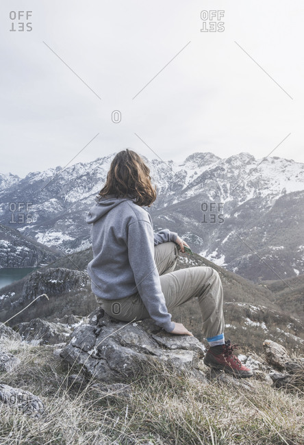 Back view of young woman sitting on a rock looking at view- Leon Province- Spain