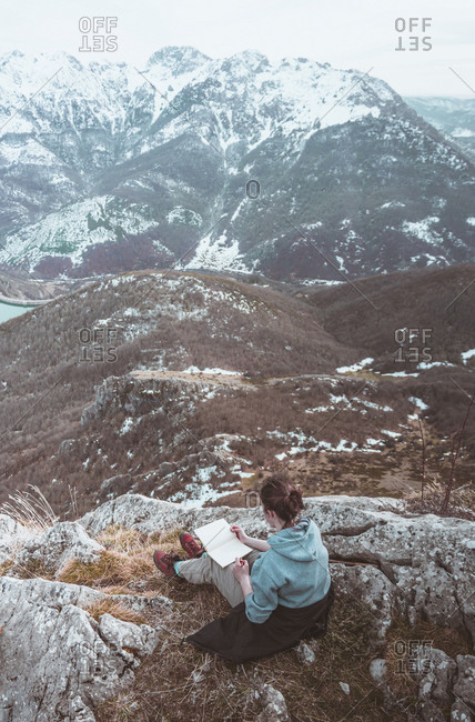Young woman sitting on a rock using sketch book- Leon Province- Spain