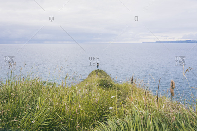 Young woman standing on grass at the cost- looking at the sea